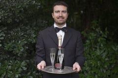Каннелюры шампанского сервировки кельнера во время торжества Стоковые Изображения RF