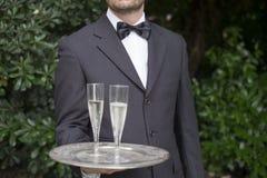Каннелюры шампанского сервировки кельнера во время торжества Стоковые Фотографии RF