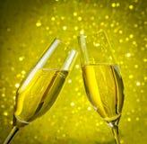 2 каннелюры шампанского с золотыми пузырями на предпосылке bokeh желтого света Стоковые Изображения