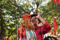 КАНТОН, †КИТАЯ «ОКОЛО январь 2017: Уличный торговец в Гуанчжоу одевал как красочный петух который дует в рожок Стоковые Фотографии RF
