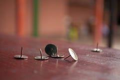 Канцелярские кнопки на деревянном столе Стоковая Фотография RF
