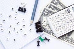 Канцелярские товары, тетрадь и деньги на белой предпосылке, конце-вверх стоковое фото
