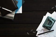 Канцелярские принадлежности на деревянном столе, взгляд сверху офиса Стоковые Изображения RF