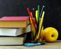 Канцелярские принадлежности (ручка, карандаш, правитель, компас) и книга на черном школьном правлении Стоковые Фотографии RF