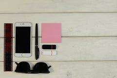Канцелярские принадлежности, солнечные очки, телефон, карточка флэш-память, фильм стоковое изображение rf