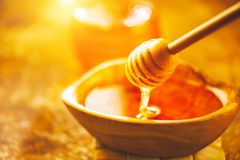 Капание меда от ковша меда в деревянном шаре Здоровый органический толстый мед лить от деревянной ложки меда стоковое изображение