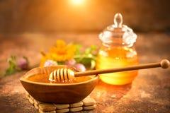 Капание меда от ковша меда в деревянном шаре Здоровый органический толстый мед лить от деревянной ложки меда стоковое фото