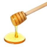 Капание меда от деревянного ковша меда изолированного на белизне Стоковые Изображения