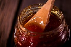 Капание меда от ковша меда   на черной предпосылке Стоковые Фото