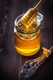 Капание меда от ложки в опарнике Стоковая Фотография
