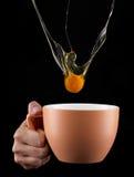 Капание яичного желтка внутри к чашке Стоковое Фото