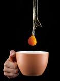 Капание яичного желтка внутри к чашке Стоковые Изображения