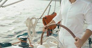 Капитан на яхте Красивый бородатый человек в белых одеждах держит его руки на катании руля на яхте акции видеоматериалы