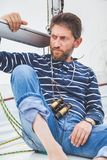 Капитан с бородой сидит на палубе яхты плавания Стоковые Фотографии RF