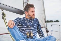 Капитан с бородой сидит на палубе яхты плавания Стоковое Фото