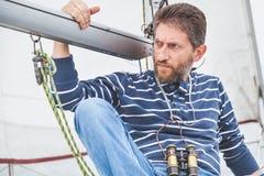 Капитан с бородой сидит на палубе яхты плавания Стоковое фото RF