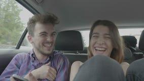 Капризная девушка переплетая ниппель парня делая шутку и смеясь пока положение в заднем сиденье автомобиля такси вися вне - акции видеоматериалы