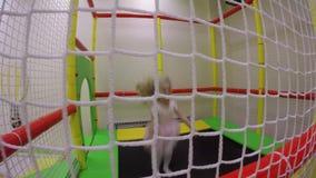 Капризная девушка скача на крытый батут в центре игры детей сток-видео