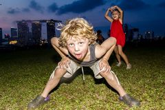 Капризные дети играя и представляя смешно на заграждении Марины, Сингапуре стоковое фото