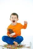 Капризный ребенк есть шоколад сидя положив ногу на ногу Стоковое Фото