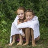 2 капризных маленькой девочки сидя на пляже в полотенце после купать в озере Лето Стоковая Фотография