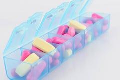 Капсула и таблетка в ежедневной коробке пилюльки Стоковые Изображения RF