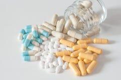 Капсулы и таблетки лекарства падая от бутылки на whit Стоковое Изображение