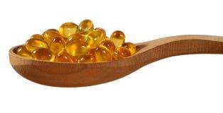 Капсулы масла рыб Omega-3 тучные в деревянной ложке на белизне Стоковая Фотография RF