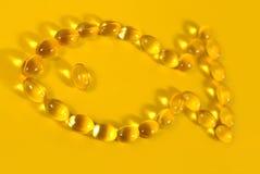 Капсулы масла рыб Omega-3 тучные сформировали в рыбах на желтом цвете Стоковое фото RF