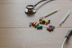 Капсула лекарства крупного плана и стетоскоп и ртуть на деревянной таблице МЕДИЦИНСКАЯ принципиальная схема стоковая фотография