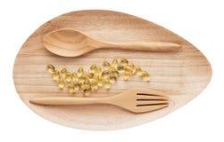 Капсулы геля масла печени трески на деревянной плите изолировали белизну Стоковое Изображение RF