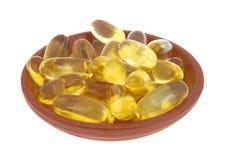 Капсулы масла печени трески в малом блюде Стоковая Фотография RF