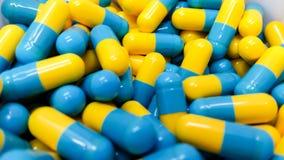 2 капсулы медицины тона на нержавеющей стали дают наркотики подносу, желтому Стоковое фото RF
