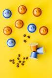 Капсулы напитка для mashine кофе и зерна на желтом copyspace взгляд сверху предпосылки Стоковые Фото