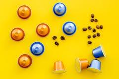 Капсулы напитка для mashine кофе и зерна на желтом copyspace взгляд сверху предпосылки Стоковое фото RF