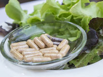 Капсулы пищевых добавок на стеклянном блюде с свежим vegetabl Стоковая Фотография RF