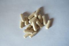 капсулы c предпосылки изолировали белизну витамина Стоковая Фотография RF