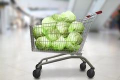 Капусты в магазинной тележкае на bokeh запачкали предпосылку магазина Органическая вегетарианская еда Стоковое Фото