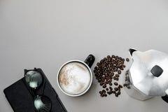 Капучино, бак кофе и и таблетка в серой предпосылке К стоковые фотографии rf