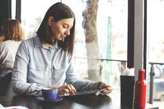 Капучино счастливой молодой женщины выпивая, latte, macchiato, чай, используя планшет и говорить на телефоне в кофейне/ба Стоковые Фотографии RF