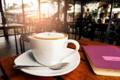 Капучино с тетрадью в кофейне Стоковая Фотография