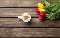 Капучино с формой сердца и букетом тюльпанов Стоковые Изображения