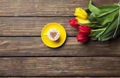 Капучино с формой сердца и букетом тюльпанов Стоковые Фото