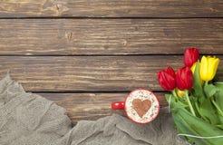 Капучино с формой сердца и букетом тюльпанов Стоковые Фотографии RF