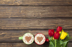 2 капучино с формой сердца и букетом тюльпанов Стоковые Фото