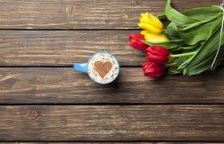 Капучино с формой сердца и букетом тюльпанов Стоковые Изображения RF