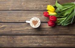 Капучино с формой сердца и букетом тюльпанов Стоковая Фотография
