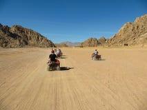 Караван ATV участвуя в гонке на высокой скорости через пустыню стоковые фотографии rf