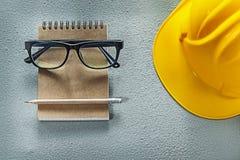Карандаш тетради стекел трудной шляпы на конкретной предпосылке Стоковое Изображение