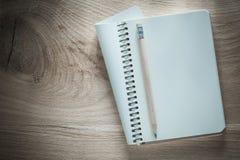 Карандаш тетради с прописями на концепции офиса деревянной доски Стоковые Фотографии RF